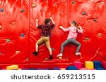 Kids Climbing On A Wall In...