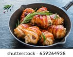 Small photo of Bacon wrapped chicken drumsticks in a black cast-iron skillet on the stone background.
