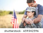 husband hugs wife in the army | Shutterstock . vector #659342596