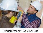 electricians taking measurements | Shutterstock . vector #659421685