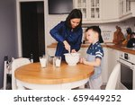 kid boy helps mother to cook in ... | Shutterstock . vector #659449252