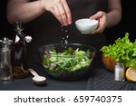 Small photo of Woman chef in the kitchen preparing vegetable salad. Healthy Eating. Diet Concept. A Healthy Way Of Life. To Cook At Home. For Cooking. The girl sprinkles sea salt in a salad on a dark background