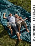 Small photo of Couple lying on unraised tent smiling