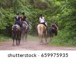 Stock photo a group of people riding horses in the forest 659975935