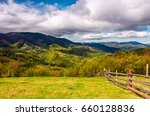 wooden fence on hillside in the rural area in mountains. beautiful countryside landscape. - stock photo
