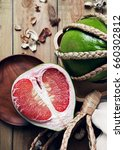 Small photo of Top view of Thailand Siam ruby pomelo fruit on wooden background. Red pomelo.