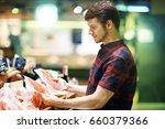man choosing meat in shop. | Shutterstock . vector #660379366