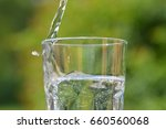 pour mineral water into a glass | Shutterstock . vector #660560068