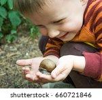 Little Boy Holding A Snail In...