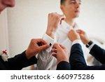 groomsmen helping groom to... | Shutterstock . vector #660975286