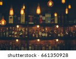 Stock photo soft focus picture of vintage lamps with blurred liquor bar in vintage photo filter style 661350928