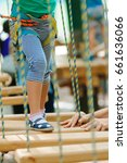 Small photo of A child accompanied by an adult moves on ropes course