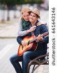 Small photo of The guy abd girl in the hat plays the guitar with a strange, keen expression