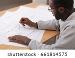 Serious smart engineer drawing a plan - stock photo