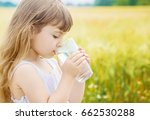 the child holds a glass of... | Shutterstock . vector #662530288