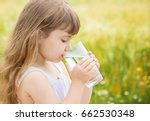 the child holds a glass of... | Shutterstock . vector #662530348