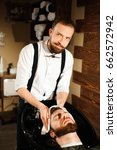master cuts hair and beard of... | Shutterstock . vector #662572942