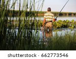 man fishing with rod while... | Shutterstock . vector #662773546