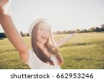 Small photo of Summer funky mood! Happy young girl on vacation in an open air spring park is making selfie, in a stylish hat, wearing casual outfit, laughing and posing
