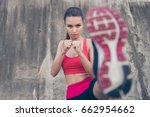 Small photo of Self defence. Focus of a young cute serious fighter, training kickboxing high kick exercise with her foot, outdoors, in pink fashionable sport outfit, trendy sneakers