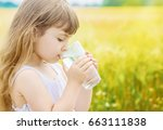 the child holds a glass of... | Shutterstock . vector #663111838
