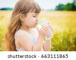 the child holds a glass of... | Shutterstock . vector #663111865