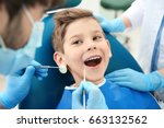 Dentist examining little boy's...