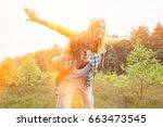 happy woman enjoying piggyback... | Shutterstock . vector #663473545