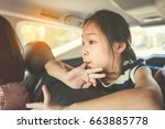 asian girl sitting in car while ... | Shutterstock . vector #663885778