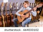 happy teenage boy choosing best ... | Shutterstock . vector #664033102