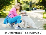 Stock photo young blonde woman is relaxing in the park with her retriever 664089352