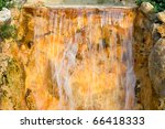 waterfall over golden rocks - stock photo