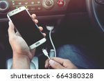 charge the battery phone in car. | Shutterstock . vector #664380328