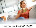 cheerful woman relaxing in sofa ... | Shutterstock . vector #664516675