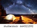 male hiker enjoying in his camp ... | Shutterstock . vector #664521592