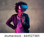 cheerful young woman wearing vr ... | Shutterstock . vector #664527385