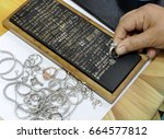 jeweler inspects silver ring...   Shutterstock . vector #664577812