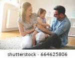 happy family sitting on floor... | Shutterstock . vector #664625806