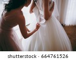 bride wears a wedding dress | Shutterstock . vector #664761526