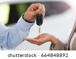 car salesman handing car keys... | Shutterstock . vector #664848892