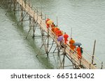 monks crossing the river on a... | Shutterstock . vector #665114002
