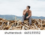 man in hat with ax sitting on... | Shutterstock . vector #665155552