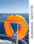Orange lifebuoy on sailing ship and blue sea - stock photo