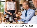 waiter holding credit card...   Shutterstock . vector #665241202
