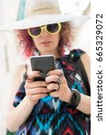 Small photo of Attractive woman in colorful dress and large sunhat wearing jewelry using smart phone on a sunny summer day. Sharing memories is always exciting