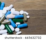 Small photo of Drug and capsule is on the wooden table Multicolored of drug and drug capsule. We are against drugs ( anti drugs )