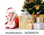 cheerful santa girl stand near the gift and New-year's tree. Copy text. Christmas greetings card - stock photo