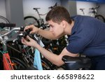 young man checking bicycle... | Shutterstock . vector #665898622