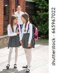 two schoolgirls talking while... | Shutterstock . vector #665967022