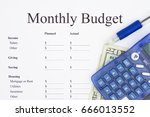 Small photo of Creating a monthly budget, A print out of a monthly budget with pen and calculator